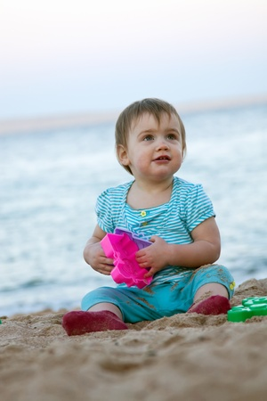 Toddler playing on sand beach photo