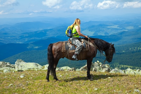 Female rider on horseback at mountains