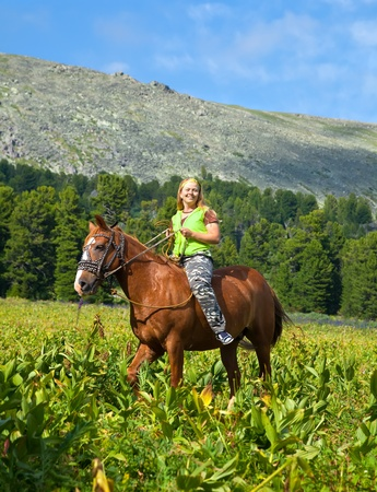 ragazza, cavalcando un cavallo senza sella alle montagne photo