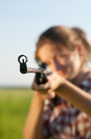 peacemaker: girl  aiming a pneumatic rifle against field. Focus on  stock only