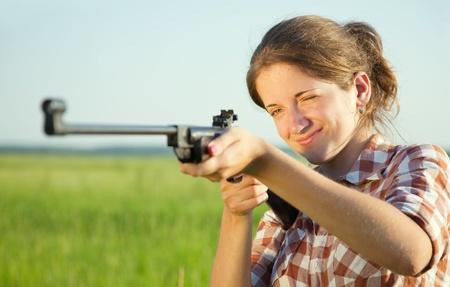 pneumatic: girl  aiming a pneumatic rifle  against summer field