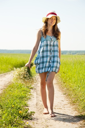 girl with bouquet of camomiles walking on country road photo