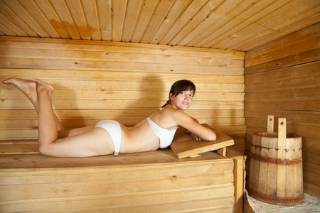 girl lying on  wooden bench in  sauna photo