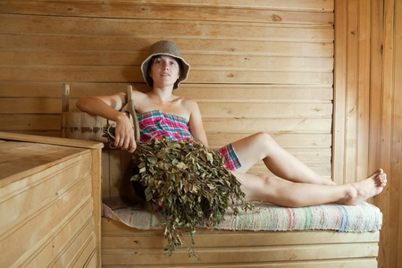 stive: girl is steamed in the sauna with birch flag broom