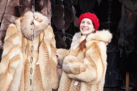 furskin: girl chooses a fur coat at market
