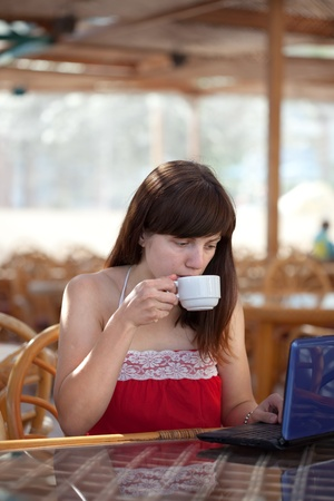 Young  woman using   laptop at resort cafe photo