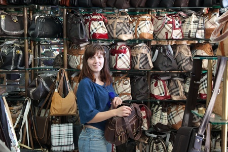 Young woman chooses bag at  shop