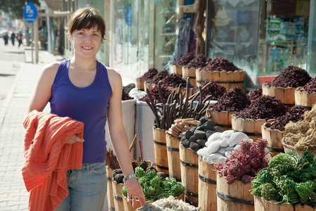 market gardener: woman  chooses herbs at oriental market
