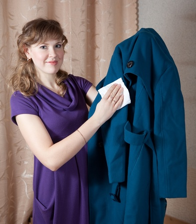 kerseymere: Woman cleaning coat  with rag  at home