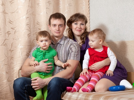 Family of four on sofa at home photo
