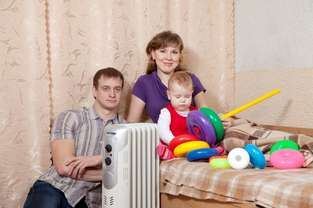 calorifer: Family  relaxing at home near oil heater