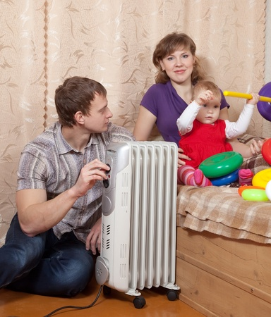 heat register: parents and child relaxing near warm radiator  in home