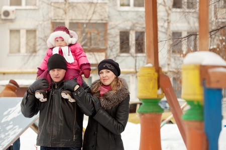 Happy parents with toddler  in winter street photo