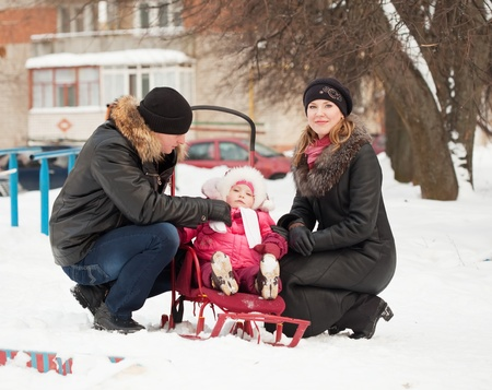 Happy parents with toddler on sled  in winter photo