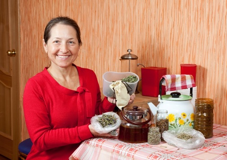 officinal: Mature woman brews herbs in a teapot at home kitchen