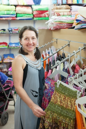 Mature woman  chooses dress at fashionable shop
