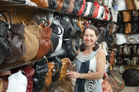 Mature woman chooses leather bag at  shop Stock Photo - 12385844