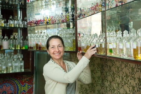 reconstituted: Mature woman chooses essential oils at  shop