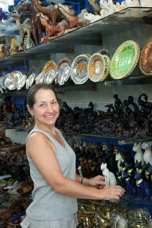 Female tourist  chooses egyptian stone cat in souvenirs shop photo