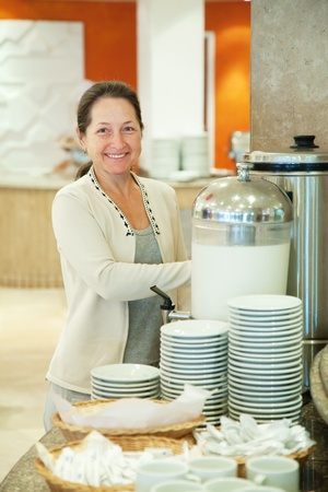 percolate: Woman pours coffee  at hotel restaurant