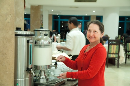 percolate: Woman pours milk to coffee at hotel restaurant
