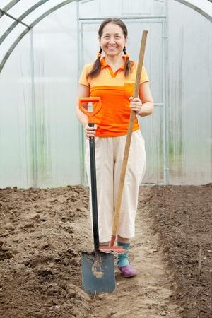 Mature gardener  with spade and rake in greenhouse  photo