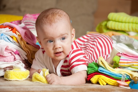 baby girl with stacked of childrens clothes photo