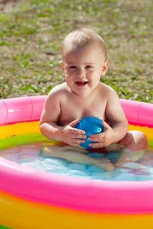 Happy baby swimming  in kid inflatable pool on lawn photo
