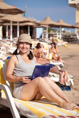 Happy mature woman sitting  with laptop at resort beach photo