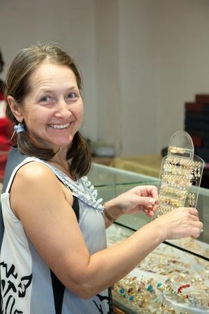 Mature woman chooses  earrings  jewelry shop photo