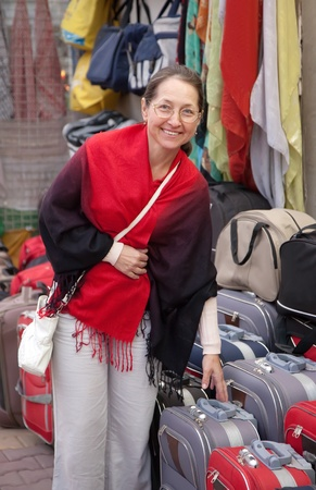 Mature woman chooses suitcase at  shop Stock Photo - 12436392