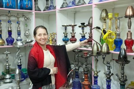 waterpipe: Mujer madura elige sheesha en la tienda de egipcio Foto de archivo