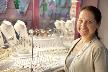 Happy mature woman  looking jewelry  counter Stock Photo - 12436388