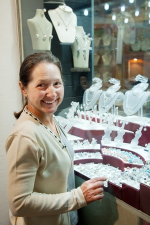 Happy mature woman   chooses jewelry at  shop photo