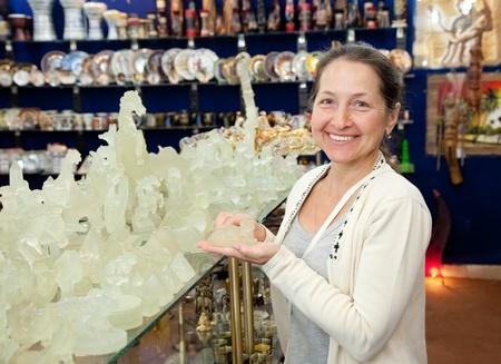 Female tourist  chooses souvenir cup in egyptian shop photo