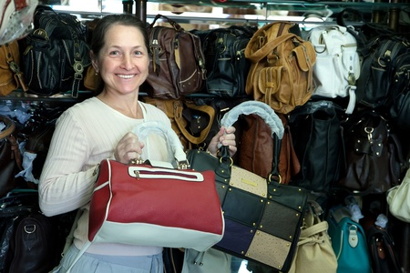 Mature woman chooses leather bag at  shop Stock Photo - 12435030