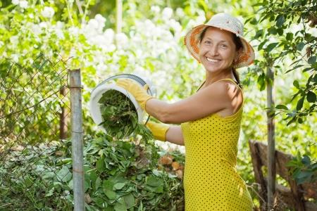 Female farmer making compost in garden photo