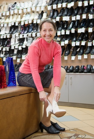 Mature woman trying shoes  for size  at shoes shop Stock Photo - 12434993