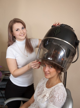 haircutting: Female hairdresser working with hair dryer