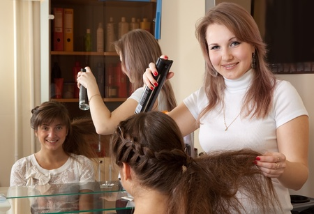 hairtician: Female hairdresser works on woman hair in salon Stock Photo