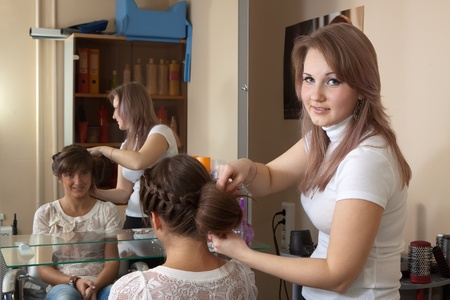 Female hairdresser works on woman hair in salon photo
