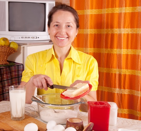 adds: Smiling woman adds margarine into dough in kitchen Stock Photo