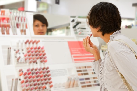 young woman is choosing lipstick at cosmetics  shop photo