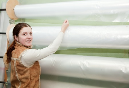 Woman  chooses polythene at foil roll at market Stock Photo - 12612751