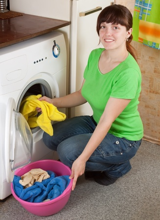 Young woman putting clothes in to washing machine and smiling Stock Photo - 12612744