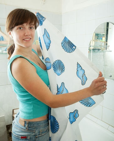 Young woman with shower curtain  in bathroom photo