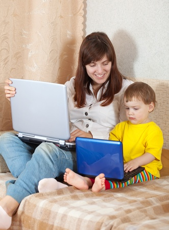 Happy woman with toddler  sitting on sofa and  using laptops in living room photo