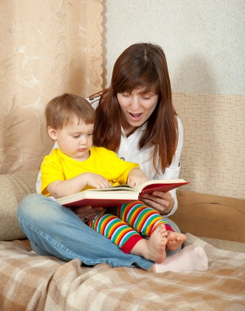 Mother and daughter reading  book together on couch in home Stock Photo - 12602386