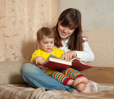 Mother showing book to her baby in home photo