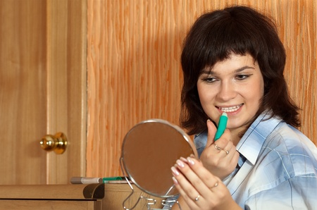 girl applying lipstick in home interior photo